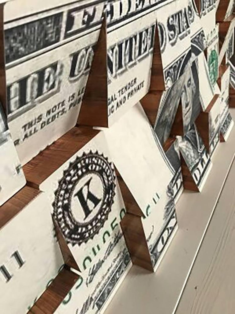 One Dollar Let Money be your God and it will torment you like the devil  This is a Conceptual Contemporary art piece, Ink Jet on Paper made out of Wooden Blocks.  This was a major project that he undertook.  Each block of wood is meticulously cut to