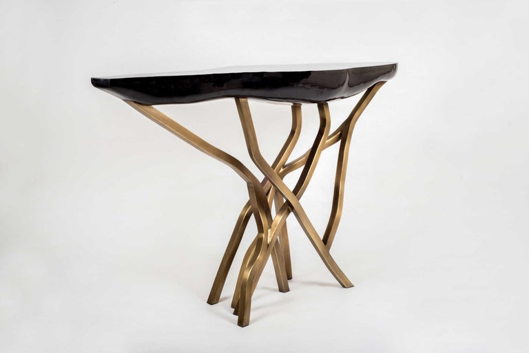 The acacia console table makes for a dramatic statement piece in any space. The amorphous shaped top is in black pen shell and the organic shaped legs are in bronze-patina brass. The shell parts are hand selected before being inlaid, creating