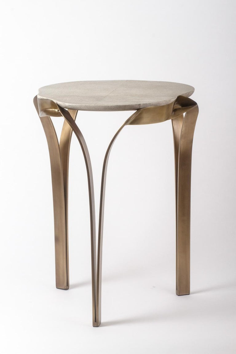 The organic design of the angel falls side table, is inspired by one of the world's most beautiful waterfalls. The amorphous shaped top in cream shagreen is elegantly wrapped with a bronze-patina brass frame that melts into the table's legs.  The