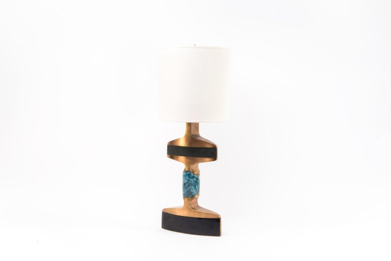 The Carmen Table Lamp is an elegant and sculptural piece that will light up your space with it's exquisite details. Inlaid in 3 different materials: black shagreen, black pen shell and blue agate and finished with bronze-patina brass accents. The