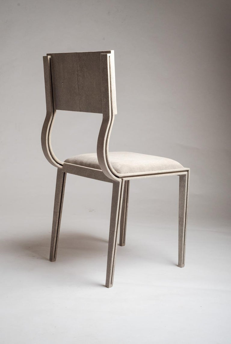 The Lola chair mixes elegance and comfort. Perfect for your dining room. The antique natural shagreen legs are unique and subtle with it's indentation details that complement the overall piece. The seat is upholstered in a luxurious soft cream linen