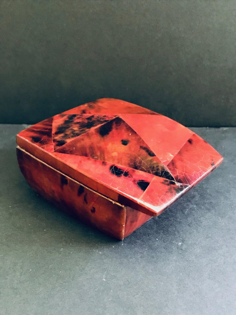 Beautiful jewelry box with hinged lid in lacquered pen-shell. Handcrafted in exotic materials with mosaic inlays in red and black. Streamline design features overlapping lid with palmwood frame with gold brass interior. Signed R&Y Augousti on