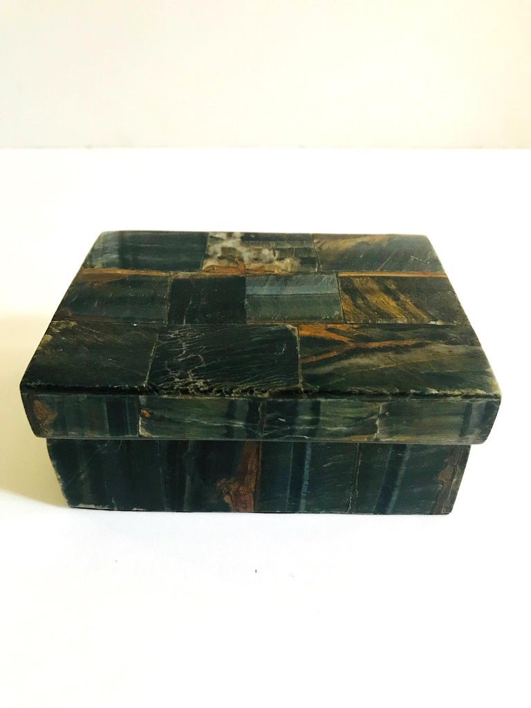 Gorgeous handcrafted lidded trinket box or decorative box in tessellated semi-precious blue tiger eye stone, also known as falcon's eye. Box features inlays of multicolored stone in hues of blue, rust, brown, and dark green. Interior box is made of
