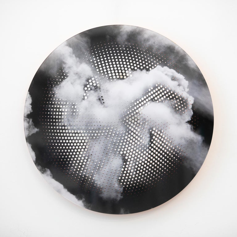A black and white pigment print of billowing clouds is perforated with a brilliant orange geometric design in this tondo by Ryan Van Der Hout. The precise, concentric design glows with orange and reflected light revealing the layers of plexiglass