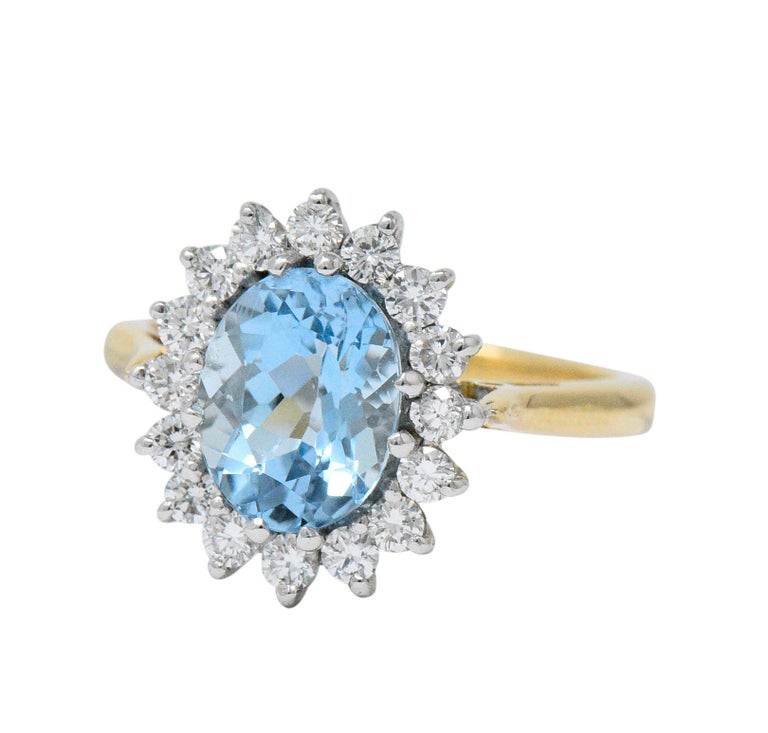 Centering a mixed oval cut aqua weighing approximately 1.85 carat, bright light blue  With a round brilliant cut diamond surround, weighing approximately 0.50 carat total, G/H color and VS to SI clarity (most VS)  The aqua is in a north, east,