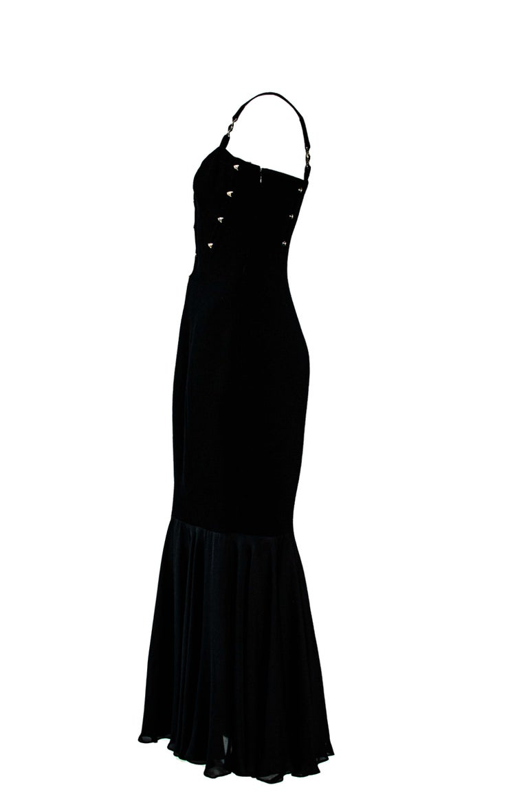 TheRealList presents: Gianni Versace's take on a mermaid silhouette. This black number was designed by Gianni Versace for his S/S 1995 collection, stuns with a form-fitting body cut and a draped bottom. The upper body features eyelets on both the