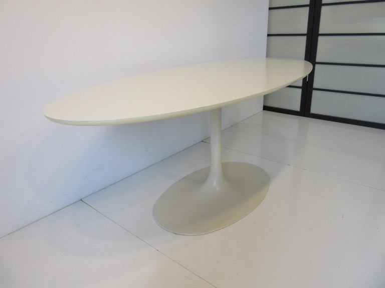 A hard to find narrow tulip writing table in the style of Eero Saarinen making this table desk perfect for that clean looking office or home office. Perfect for the lap top with an oval Formica topped surface, rolled edge and cast metal tulip base