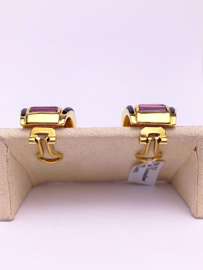 These 18 karat yellow gold earrings are designed with a row of Baguette Cut Pink Tourmaline stones set down the center with Black Onyx borders. The earrings measure approximately 3/4