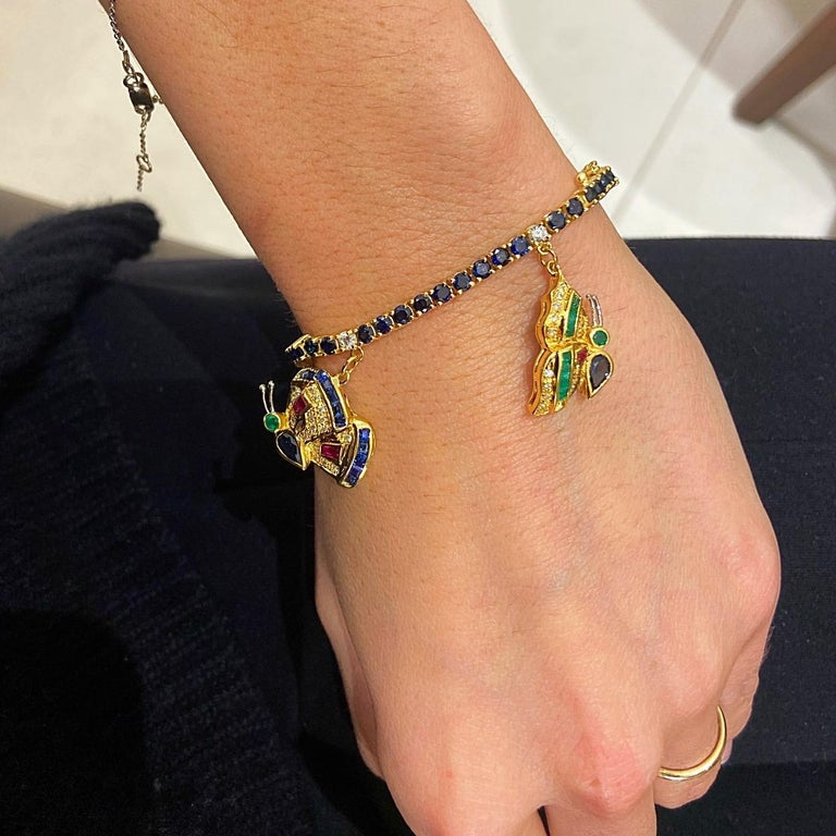 Created by the famed jewelers Sabbadini of Italy, this 18KT yellow gold charm bracelet is quite the unique piece.The blue sapphire bracelet is adorned with five butterfly charms, each detailed with diamonds, emeralds,rubies, blue and yellow