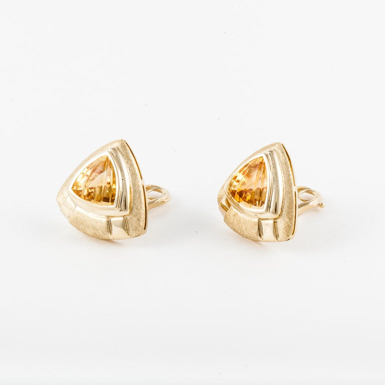 18K yellow gold earrings by Sabbadini.  The center stones are citrines which are stair step cut on top.  The finish is both polished and textured.  These are clip style earrings which measure 1-1/16