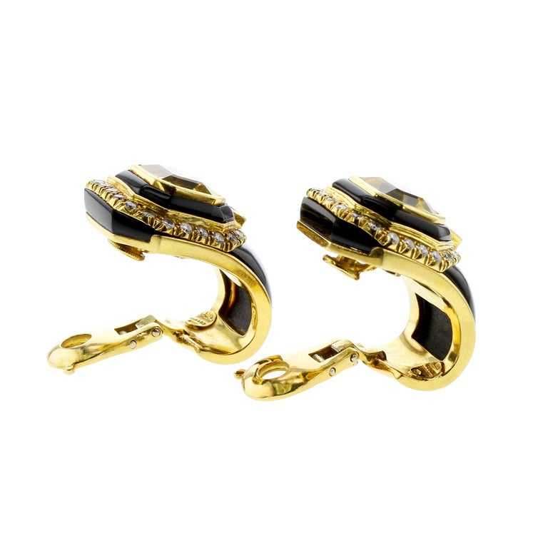 An elegant and beautiful pair of octagonal shape step-cut yellow sapphire clip-on earrings set in 18kt yellow gold. Each sapphire weighs approximately nine carats, bordered with black onyx, and further clustered with white round, brilliant-cut