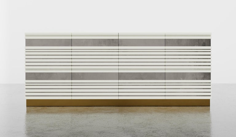 The Sabine credenza features a linear lacquer body with silver leaf inlay set on a metal plinth the standard interior features adjustable shelves on the two side bays and can be customized to your needs. Fully custom and made to order in California.