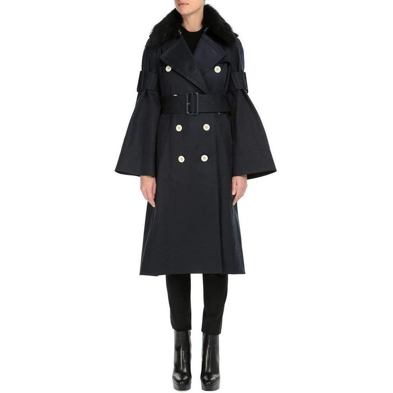 Double-breasted trench coat features buckle belt bell sleeves and a removable fur collar. Button epaulettes. Raglan sleeves. Self-belt loops. Angled welt front pockets. Shoulder yoke and inverted pleat with button closure at back. Hook-and-eye