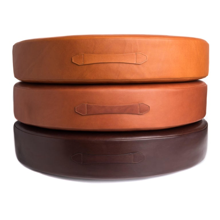 Stacked to store or sit and individual to use for floor seating, these round leather floor cushions can easily be moved to meet your needs. These cushions were designed as a set but are sold individually. Materials: Foam, Bovine Leather. Individual