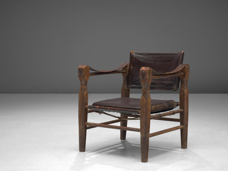 Safari chair, oak and leather, Europe, 1940s.  Robust yet stately safari chair that gained a very rich patina. This armchair features wonderfully carved wooden legs that raise up and hold up the leather straps that function as armrests. These