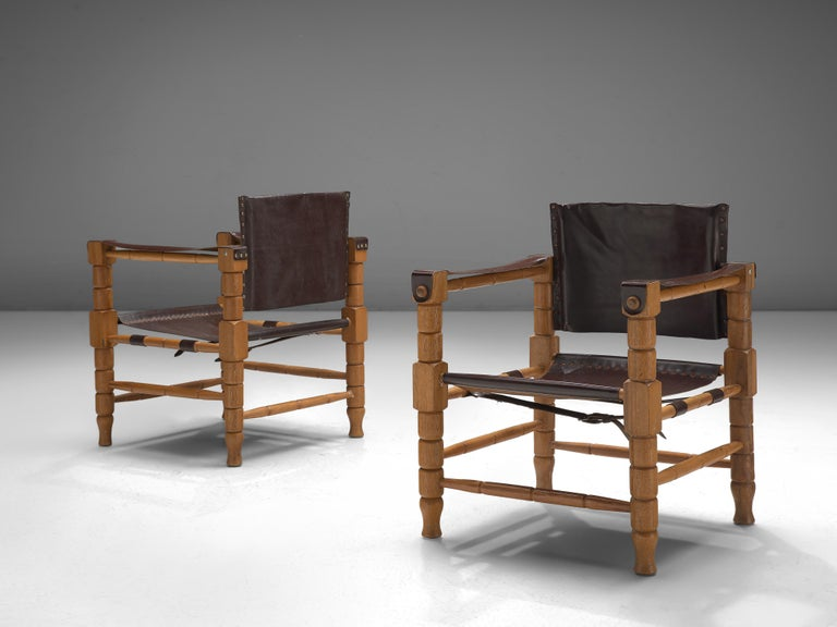 Safari chair, beech, eather, Europe, 1940s  Robust yet stately safari chairs with a rich patina. These chairs feature wonderfully carved wooden frames, with sculpted forms. The frame holds the leather straps that function as armrests and the