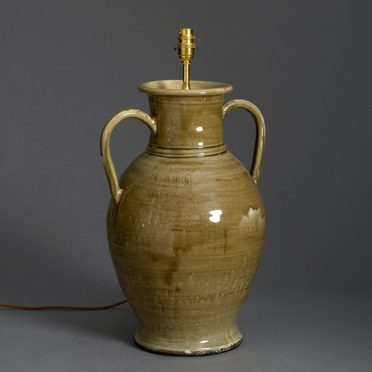 A large sage green glazed pottery two-handled vase now mounted as a lamp.