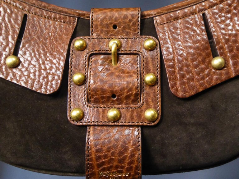 Circa 1990 France  Beautiful Saharienne bag in tawny leather and brown suede by Yves Saint Laurent Rive gauche dating from 1995. Flap tabs and fake buckle studded with brass balls. Small strap with brass rings and interior in brown satinwith