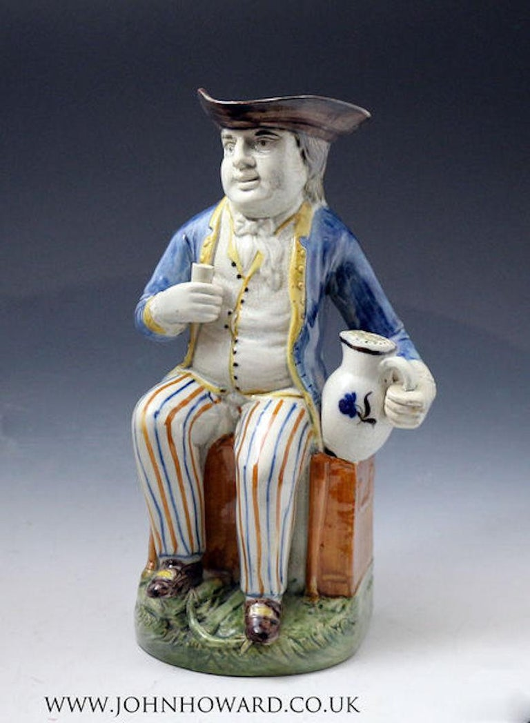 Prattware pottery Toby Jug known as the Sailor. The well-attired figure has exceptional quality decorations in the Prattware color palette. He is shown seated on a chest with a benign smile holding a beaker and frothing jug of ale. The base of the