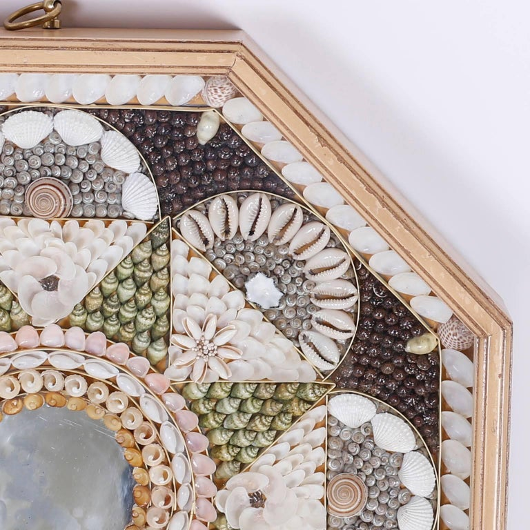 Sailors valentine composed in precise geometric patterns using an impressive array of petite seashell specimens with a centre mirror. Presented in an octagon shaped shadow box.