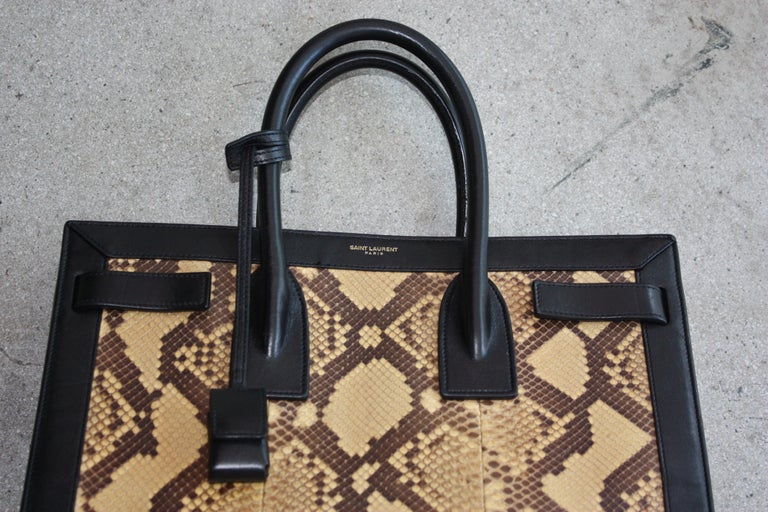 Saint Laurent black leather and yellow/brown python handbag. Lock included. Authenticity cards and dust bag included. Never been used.  Price firm.