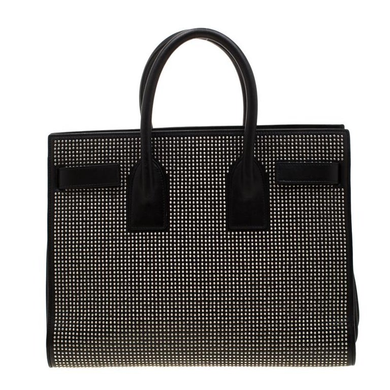 This Sac de Jour tote by Saint Laurent has a structure that simply spells sophistication. Crafted from black leather, the bag is held by double top handles and flaunts a studded exterior. The tote comes with a suede and fabric-lined interior with