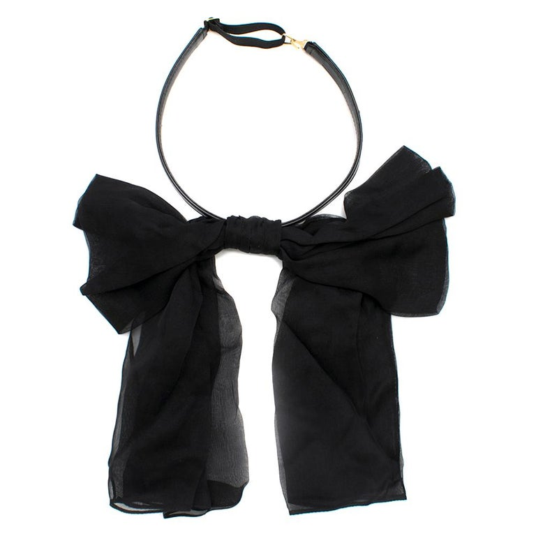 Saint Laurent Bow In Black Silk Muslin With Leather Collar  Black Silk Bow Adjustable Collar Metal Plaque With Engraved Saint Laurent Signature Made in Italy  Please note, these items are pre-owned and may show some signs of storage, even when
