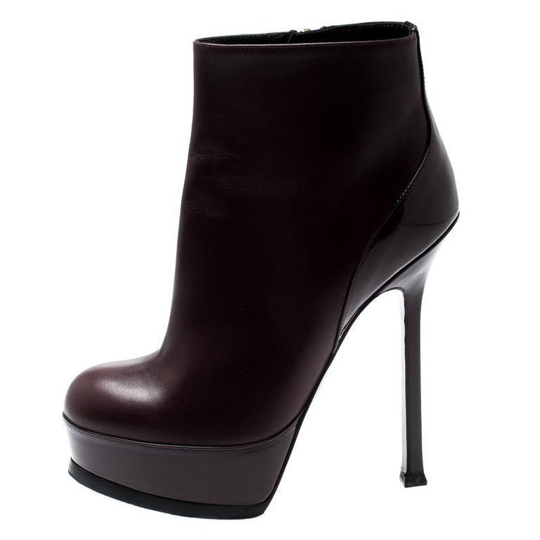 Fashioned by Saint Laurent, these ankle booties are for fashionable souls like you. Constructed using burgundy leather, they feature side zippers, platforms, and 13.5cm heels. The sleek shape gives them the extra touch of style.  Includes: Original