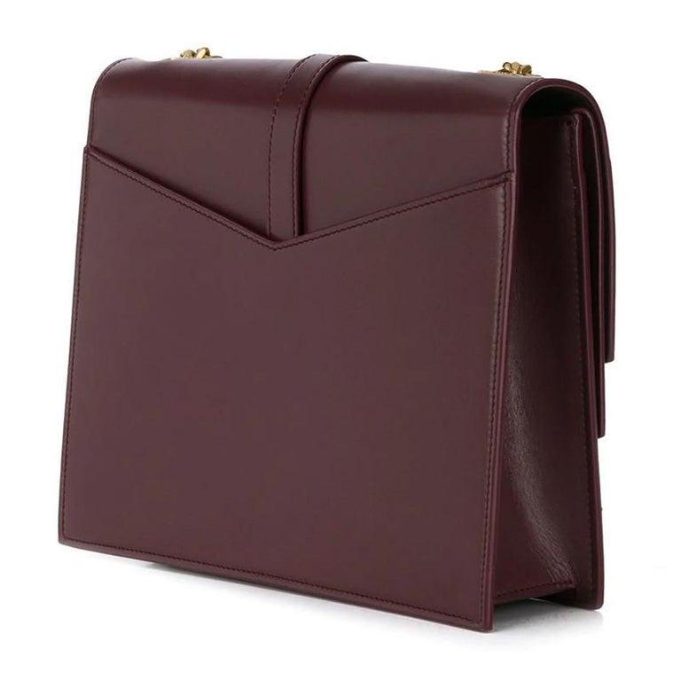 This bag is made with burgundy smooth calf leather and is the medium model. The bag features a triple v-flap, gold tone hardware, a long gourmette (a jewellery chain) shoulder strap, metallic YSL logo on front flap and black interior lining with