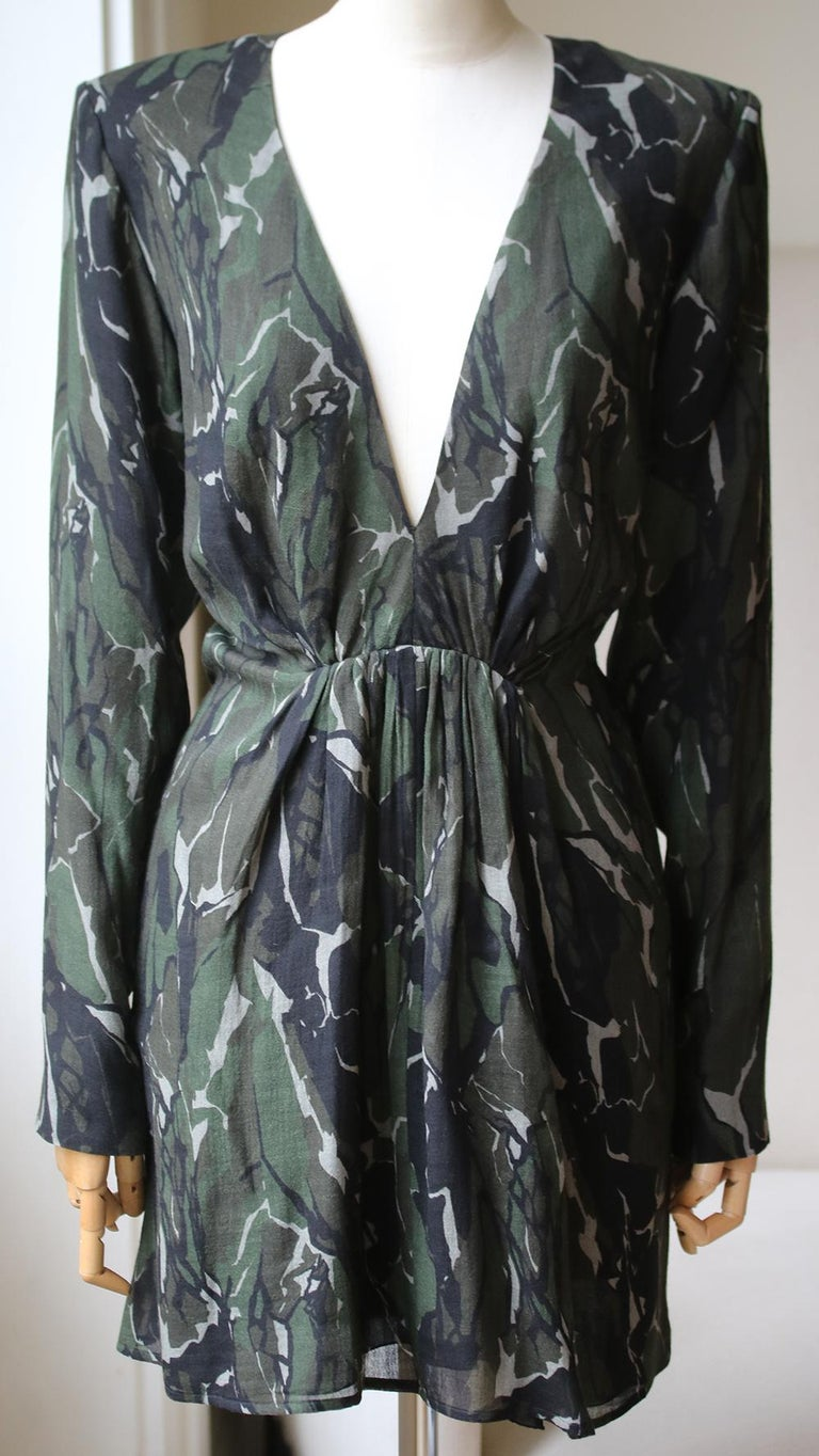 Black and green virgin wool camouflage long-sleeve mini dress from Saint Laurent featuring a v-neck, long sleeves, a fitted waist, a short length, a slim fit and a camouflage print. 100% Virgin wool. Contrast Fabric: 100% polyamide. Lining: 100%