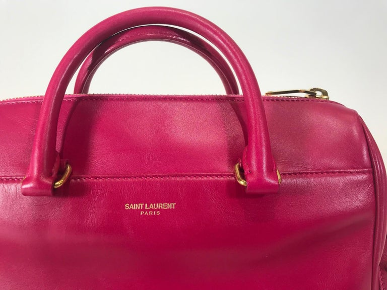 Pink leather. Gold-tone hardware. Zip closure at top. Dual rolled top handles. Single flat shoulder strap. Single slit pocket at front. Tonal suede lining. Single zip pocket at interior wall.