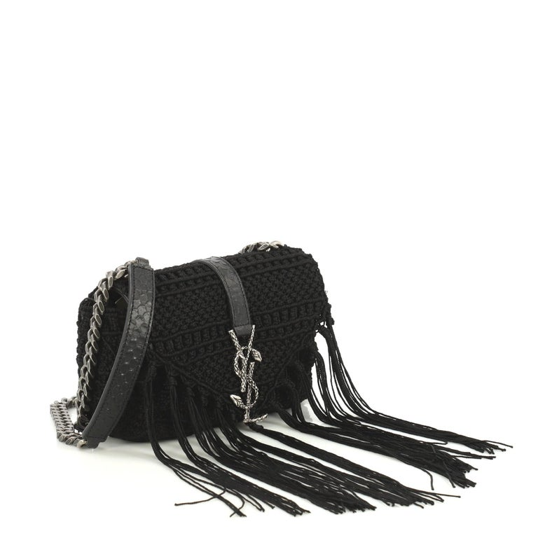 This Saint Laurent Classic Monogram Crossbody Bag Crochet Over Leather Baby, crafted from black crochet over leather, features chain link strap with leather shoulder pad, cascading fabric fringes and aged silver-tone hardware. Its hidden magnetic