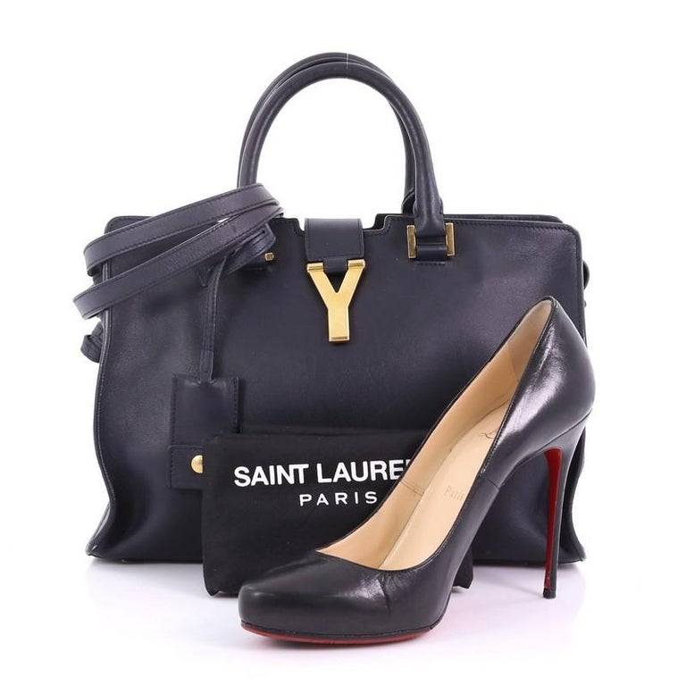 This Saint Laurent Classic Y Cabas Leather Small, crafted from navy leather, features dual rolled leather handles, signature Yves Saint Laurent's 'Y' top flap hardware piece, protective base studs, and gold-tone hardware. Its top zip closure opens