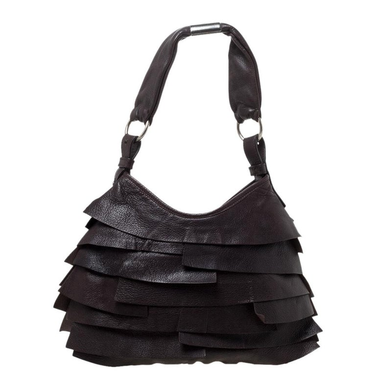 The St. Tropez hobo by Saint Laurent is a unique creation that will instantly charm you. It is crafted from leather in a dark brown shade and styled with ruffles on the exterior. It has a spacious suede interior that can easily carry all your daily