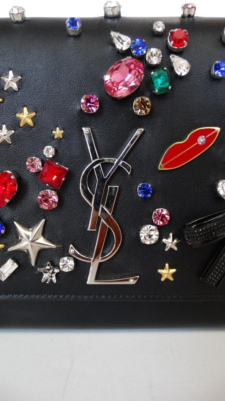 The most magical embellished bag from Saint Laurent's Fall/Winter 2016 collection! Made of a soft black leather and decorated all over with rhinestones, bows, stars, moons, lips and music notes!