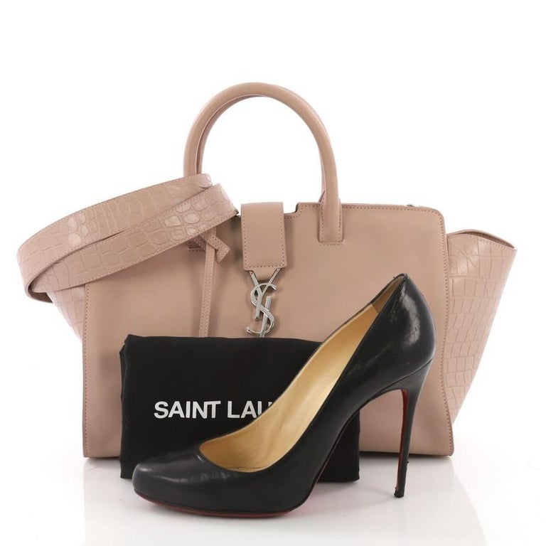 This Saint Laurent Monogram Cabas Downtown Leather with Crocodile Embossed Leather Small, crafted from nude leather with crocodile embossed leather, features dual rolled handles, YSL metal logo at the front, and silver-tone hardware. Its magnetic