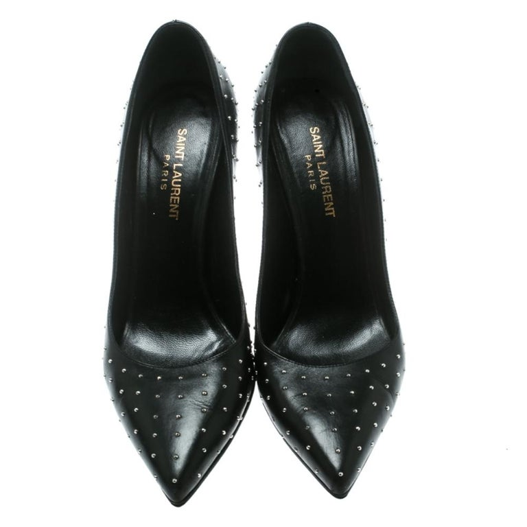 Look sparkling and pleasant in this pair of enchanting pumps from Saint Laurent Paris! These black pumps have been crafted from leather and styled with pointed toes. They flaunt silver-tone studs adorning the exterior and come equipped with