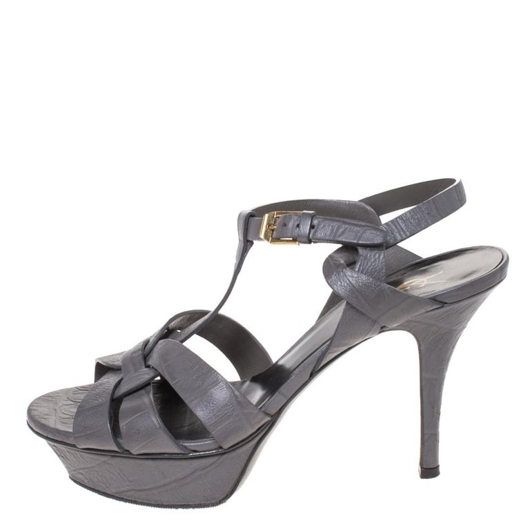 One of the most sought-after designs from Saint Laurent is their Tribute sandals. They are such a craze amongst fashionistas around the world, and it is time you own one yourself. These grey ones are designed with croc-embossed leather straps, ankle