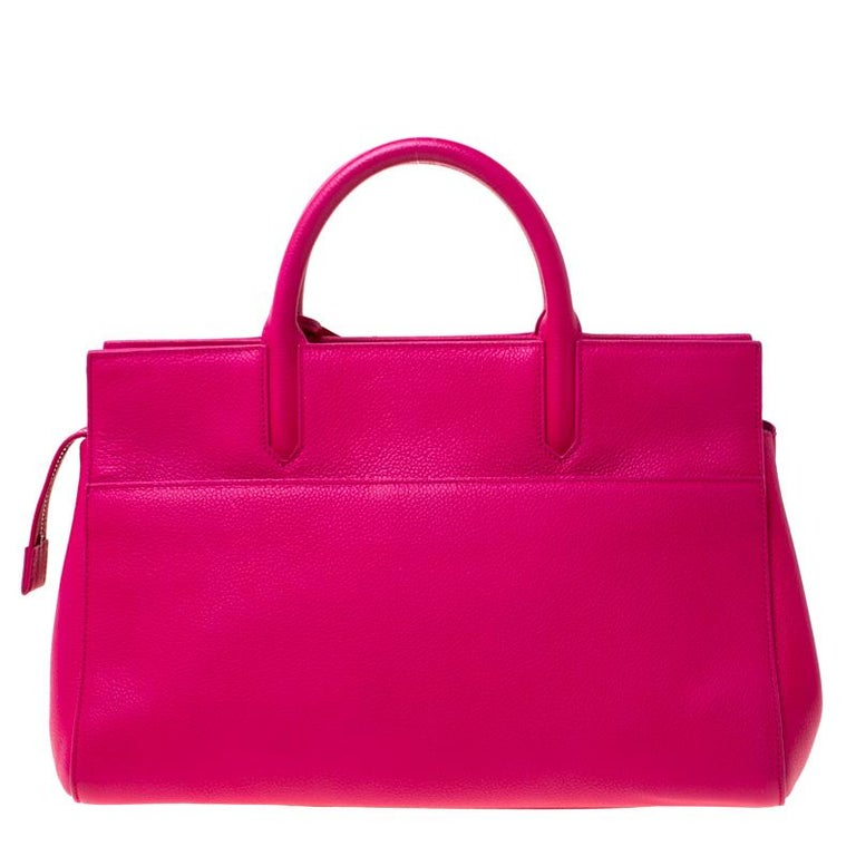 This fuschia pink Cabas Rive Gauche tote bag from Saint Laurent Paris is ideal for everyday use. Exuding an aura of luxury and elegance, this bag is crafted from leather and is detailed with a leather tag featuring YSL motif in silver-tone. The bag