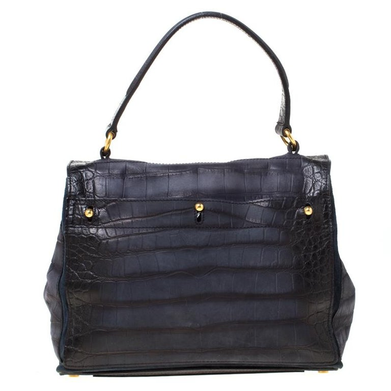 The epitome of bold yet feminine style, this Saint Laurent Paris Muse Two satchel is perfect for professional settings and formal outings. It features a navy blue croc-embossed leather and suede body with a flap silhouette and secured with a