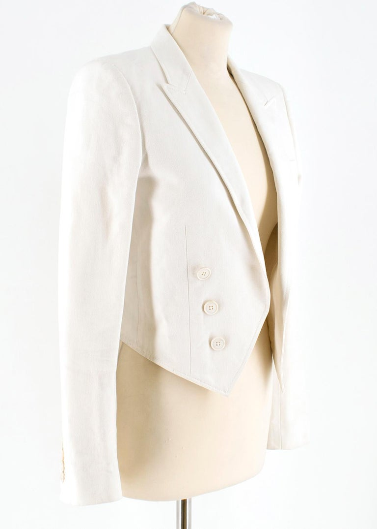Saint Laurent Runway cropped white blazer  - White, cotton drill  - Peak lapels, long sleeves - Heavily padded shoulders, decorative buttons on cuffs  - Single chest welt pockets - Angular hem  - Open front, decorative double breasted fastening  -