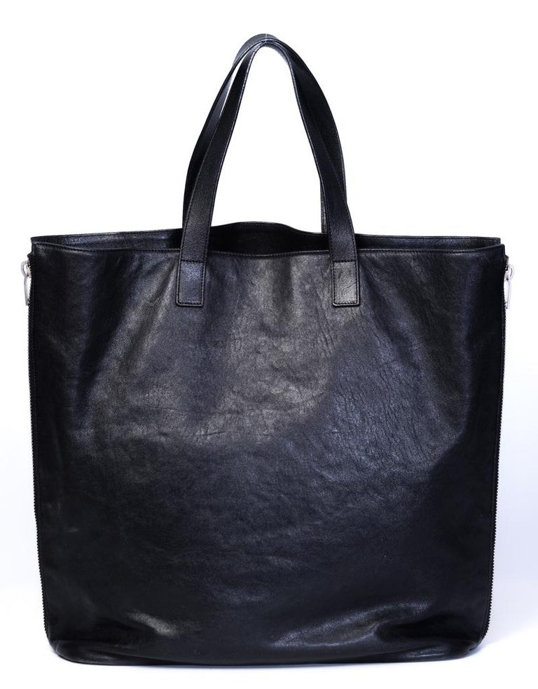 This tote is made of calfskin leather in black and features dual flat leather strap top handles, an open top, black grosgrain interior lining and the tote is adjustable by two zippers on the both sides of the bag.  COLOR: Black MATERIAL: