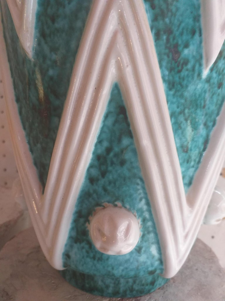A turquoise glazed ceramic vase with white ornamental motifs made by the Sainte-Radegonde workshop and the Ateliers Primavera.