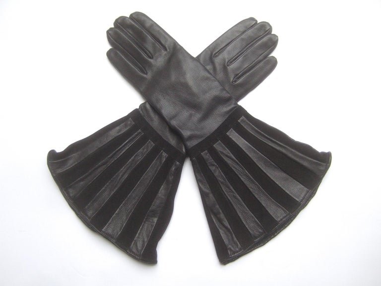 Saks Fifth Avenue Avant-garde black leather & suede trim gloves c 1980s  The chic gloves are constructed with smooth buttery soft leather. The wide flared openings are designed with striped bands that alternate from smooth black leather to plush