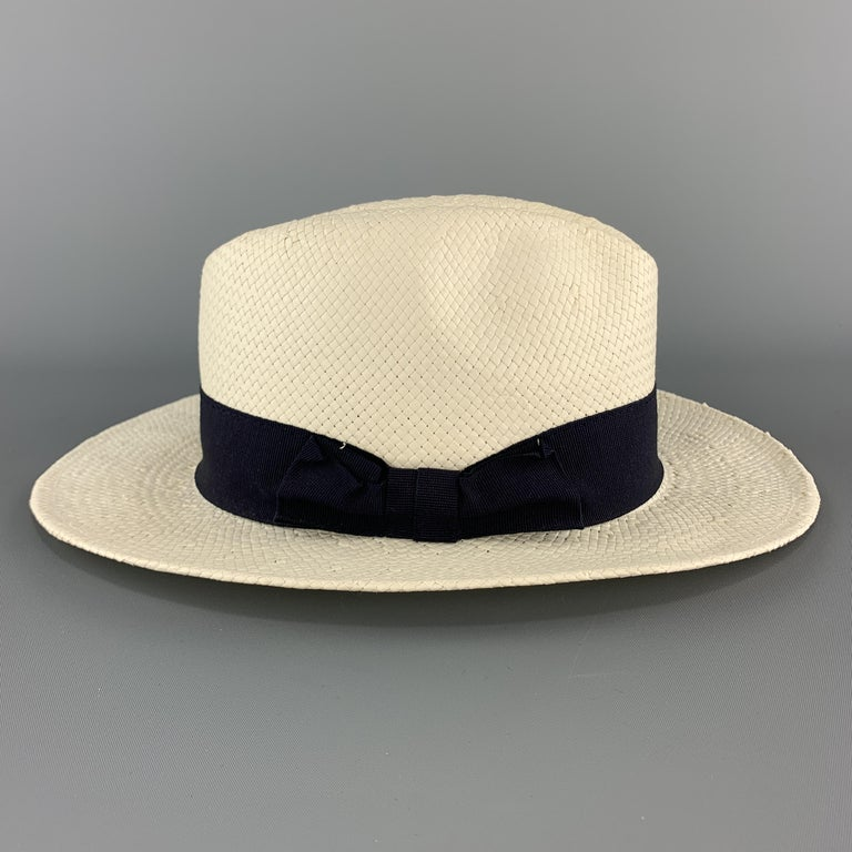 SAKS FIFTH AVENUE fedora comes in cream woven straw with a navy blue ribbon stripe. Made in Italy.  Excellent Pre-Owned Condition. Marked: (no size)  Measurements:  Opening: 23 in. Brim: 2.25 in. Height: 4.5 in.