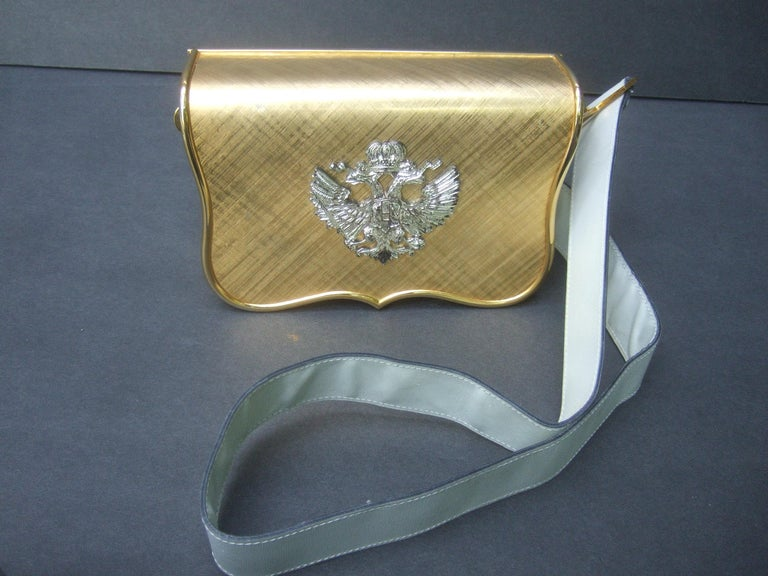 Saks Fifth Avenue Italian gilt metal eagle emblem white leather shoulder bag c 1970s The unique handbag is adorned with an ornate silver metal double headed eagle medallion mounted onto the brushed gold metal flap cover  The structured gilt metal