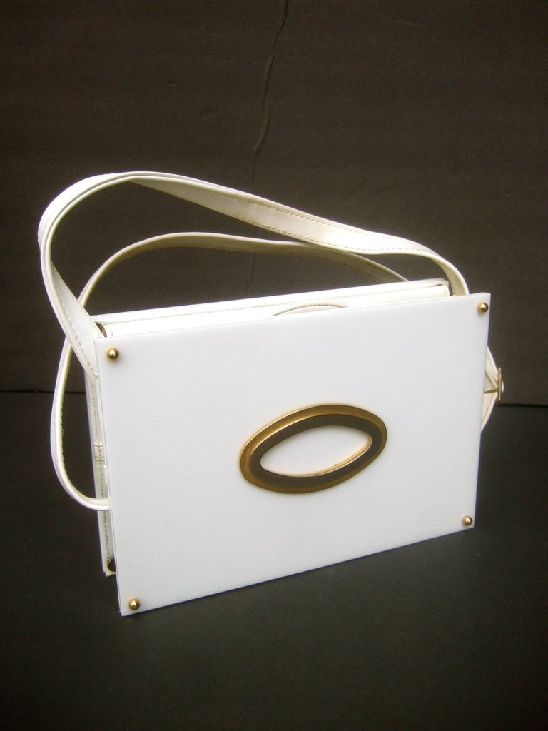 Saks Fifth Avenue mod white lucite tile handbag c 1970s The sleek retro handbag is designed with a pair  of white lucite rectangular panels on both the  front and back exterior sides  The front exterior panel is designed with a pair of elongated
