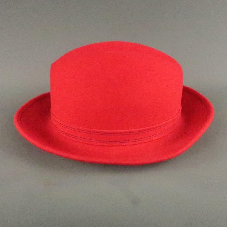 SAKS FIFTH AVENUE hat comes in a red felt wool with contrast stitching, and a feather accent.  Very Good Pre-Owned Condition. Marked: ( no size )  Measurements: Opening: 22.8 in. Brim: 2.8 in. Height: 5.5 in
