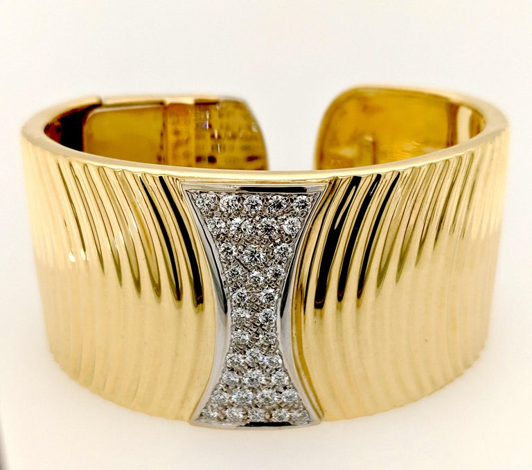 The Diamond cuff bracelet designed by Sal Praschnik is crafted in 18 karat yellow gold and features (37) round diamonds weighing 1.41cttw with a color of G/H and a clarity of SI1. The bracelet is 1, 1/4