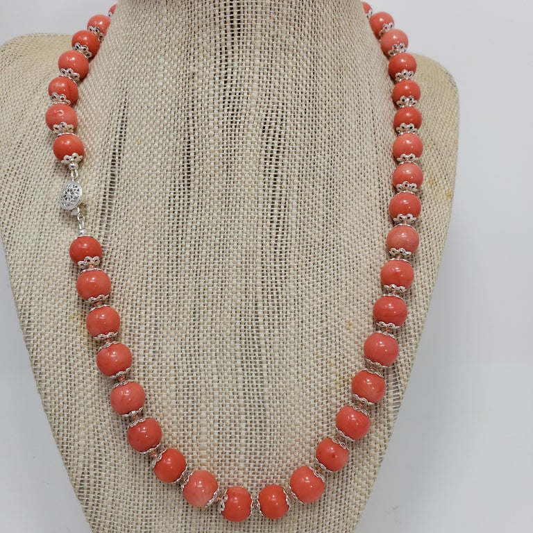 A luxurious beaded salmon coral necklace, decorated with sterling silver accents and a filigree clasp. Fit for royalty!  Hallmarks: 925 Each bead approximately 10mm in diameter